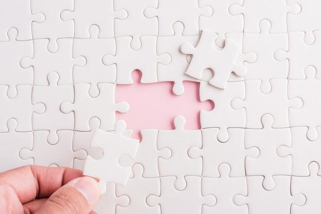 Trzymanie za rękę ostatniego kawałka układanki z białego papieru ostatnie elementy ułożone na miejscu do rozwiązania problemu
