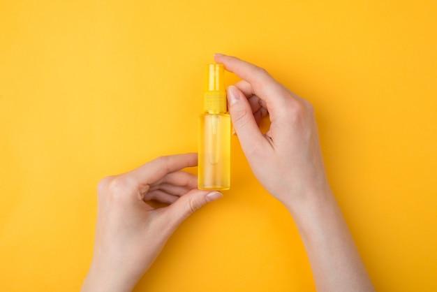 Trzymanie zarazków z dala od koncepcji rąk. górne nad głową zbliżenie zdjęcia kobiety trzymającej butelkę środka dezynfekującego do rąk w sprayu na jasnym tle w kolorze żółtym