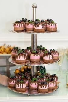Trzypoziomowa taca z ciastami na stole bankietowym. święta i wydarzenia.