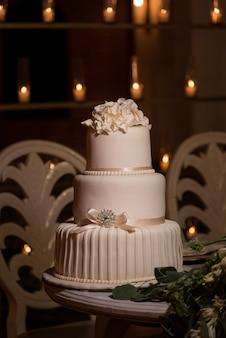 Trzypoziomowy biały tort weselny z fondantem, zwieńczony kwiatami buttercream