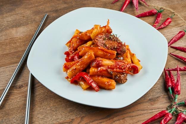 Tteok-bokki - tradycyjne danie kuchni koreańskiej, smażone placki ryżowe z żeberkami wieprzowymi w białej płytce na drewnie. ścieśniać. selektywne ustawianie ostrości