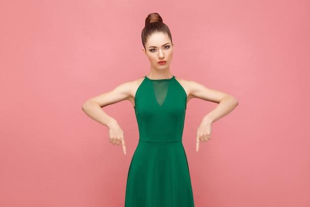 Tu i teraz! kobieta palcem wskazującym na miejsce. koncepcja ekspresji emocji i uczuć. strzał studio, na białym tle na różowym tle