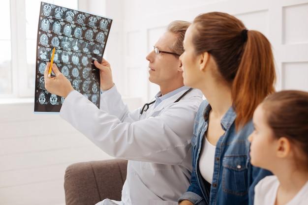 Tu jest problem. wykwalifikowany, opiekuńczy skoncentrowany chirurg wskazujący na skan mózgu mówiący o niektórych problemach i upewniający się, że wszystko jest zrozumiałe