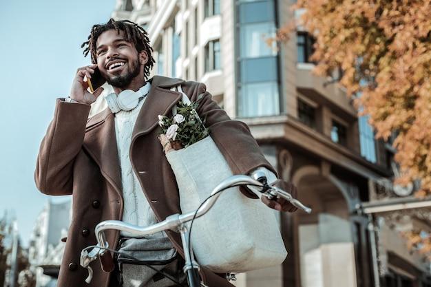 Tu jestem. przystojny mężczyzna trzymając torbę na ramię idąc do domu