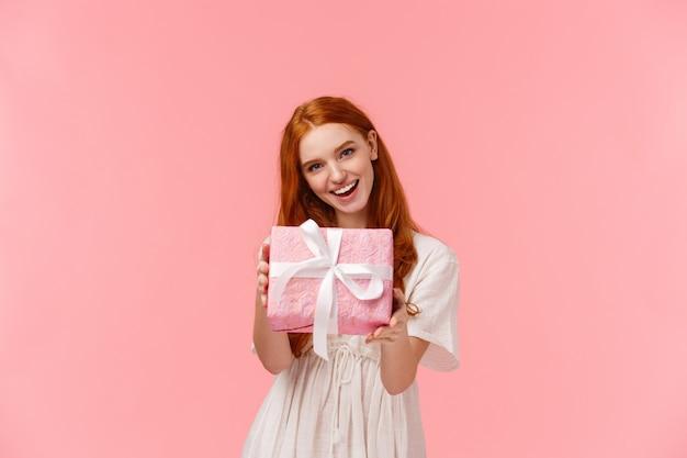 Tu masz. urocza i delikatna, kobieca ruda kobieta daje ci prezent, trzymając zapakowane pudełko