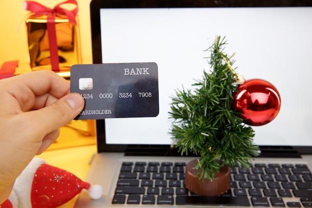 Tula, 28 09 19: koncepcja zakupów online. karta kredytowa i laptop z prezentami świątecznymi i pudełkami.