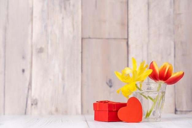 Tulipanowa kompozycja kwiatowa w szklanym wazonie z pozdrowieniami serca, konewka wystrój na ścianie tle drewniany stół, bliska, koncepcja projektowa dzień matki.