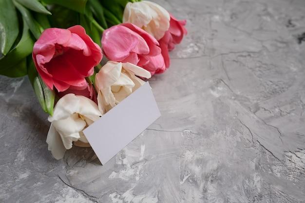 Tulipany i kartkę z życzeniami na szarym tle grunge