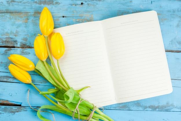 Tulipany i notatnik na niebieskim stole