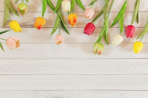Tulipany kwitną na lekkim drewnianym tle.