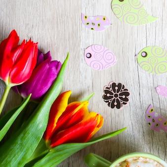 Tulipany na drewniane z dwiema filiżankami kawy. pocztówka z zaproszeniem na dzień matki lub międzynarodowy dzień kobiet. wiosenne kwiaty, kolorowe ptaki. ręcznie robione origami. mocne pastele. cappuccino z cynamonem.