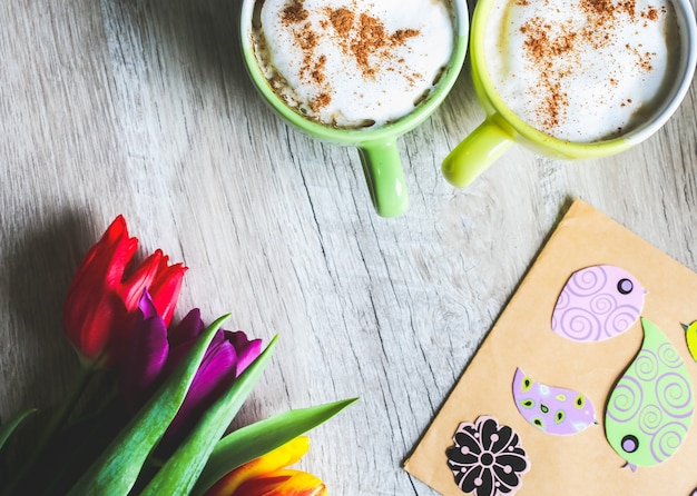 Tulipany na drewniane z dwiema filiżankami kawy. pocztówka z zaproszeniem na dzień matki lub międzynarodowy dzień kobiet. wiosna papierowe ptaki na papierowej kopercie. ręcznie robione origami. mocne pastele. cappuccino.