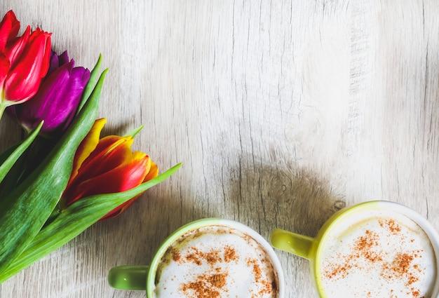 Tulipany na drewnianym tle z dwiema filiżankami kawy. pocztówka z zaproszeniem na dzień matki lub międzynarodowy dzień kobiet. mocne pastele. cappuccino z pianką cynamonową i kwiatami.