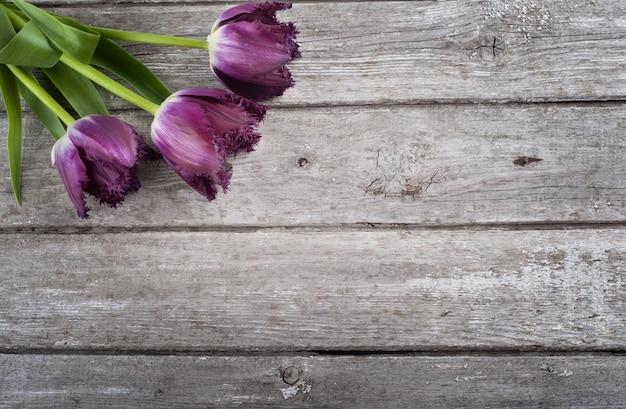 Tulipany na stajni drewna tle