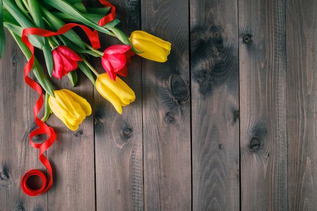 Tulipany na stole z ciemnego drewna
