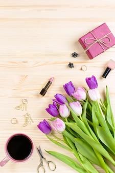 Tulipany, pudełko i akcesoria mody na drewnianym biurku