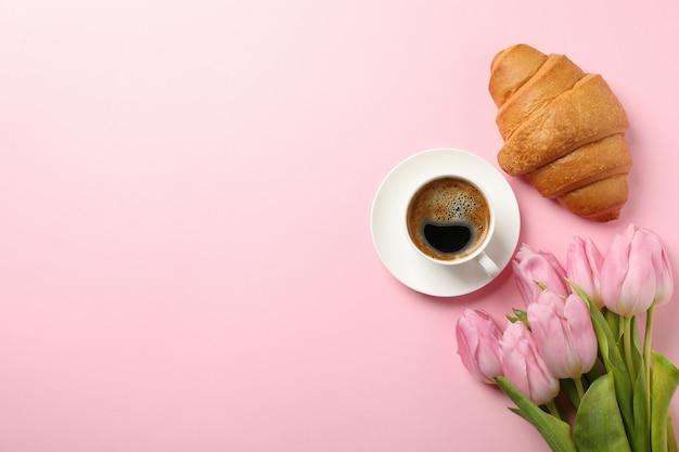 Tulipany, rogalik i filiżankę kawy na różowym tle, widok z góry