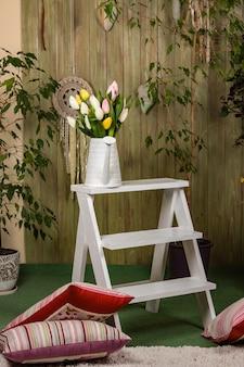 Tulipany w białej konewce na białych schodach. wnętrze w stylu prowansalskim. rośliny domowe i zielona drewniana ściana z ręcznie wykonanym wystrojem.