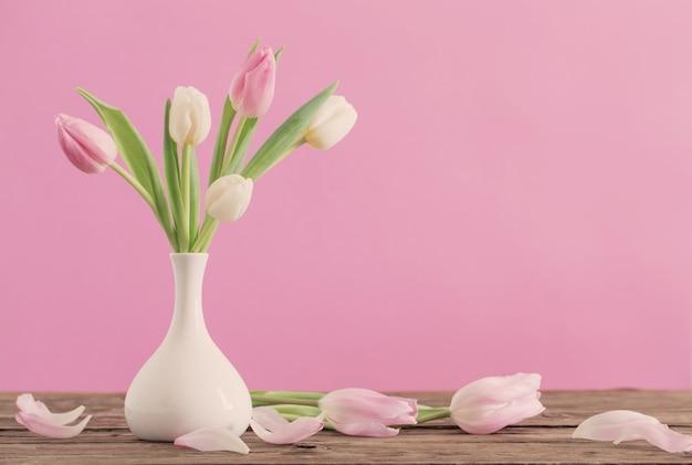 Tulipany w białym wazonie na różowym tle