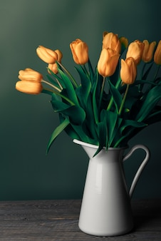 Tulipany w dzbanku. klasyczna martwa natura z bukietem delikatnych kwiatów tulipanów w białym dzbanku vintage na zielonej ścianie i starym drewnianym stole.