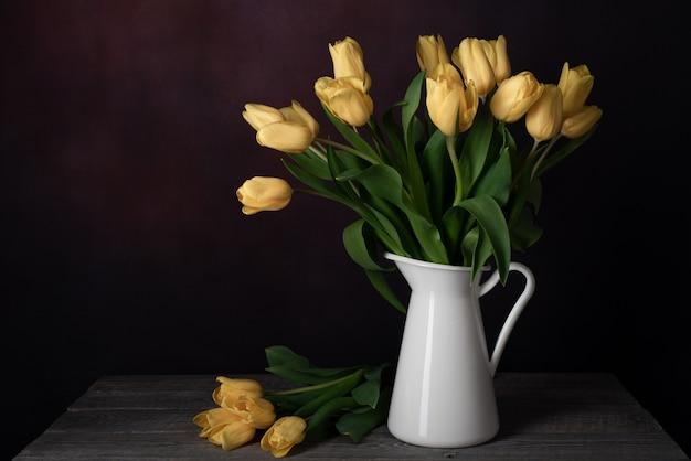 Tulipany w dzbanku. klasyczna martwa natura z bukietem żółtych kwiatów tulipanów w vintage białym dzbanku na ciemnym tle i starym drewnianym stole.