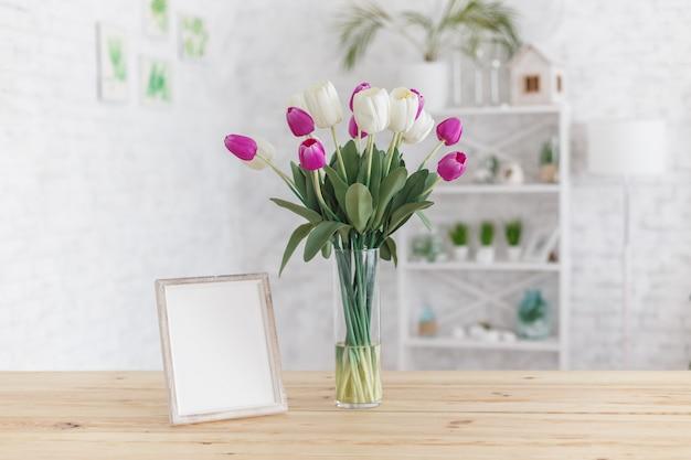 Tulipany w wazie na drewnianym stole. skandynawskie wnętrze. makieta.