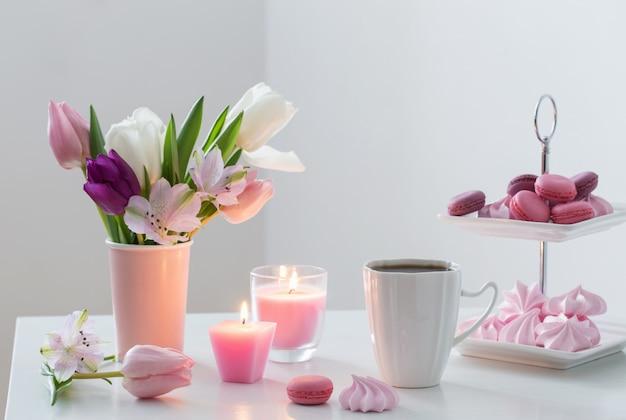 Tulipany w wazonie i filiżanka kawy z deserem