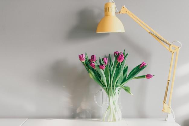 Tulipany w wazonie i żółta lampa w domowym wnętrzu na szarej ścianie