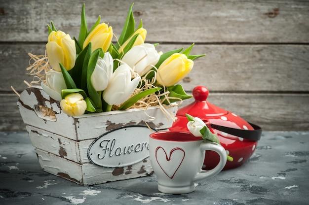 Tulipany z filiżanką i czerwonym czajnikiem w kropki