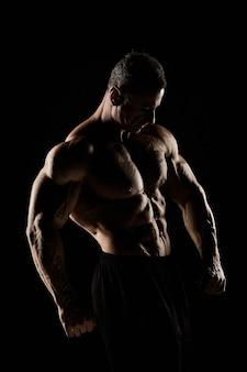 Tułów atrakcyjnego męskiego ciała budowniczego na czarnym tle.