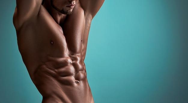 Tułów atrakcyjnego męskiego ciała budowniczego na niebieskim tle.