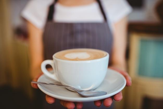 Tułów baristy serwującej kawę w stołówce