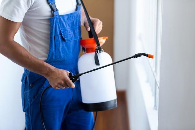 Tułów pracownika ochrony przed szkodnikami opryskiwaczem