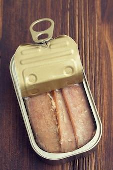 Tuńczyk w żelaznym pudełku na drewnianej powierzchni