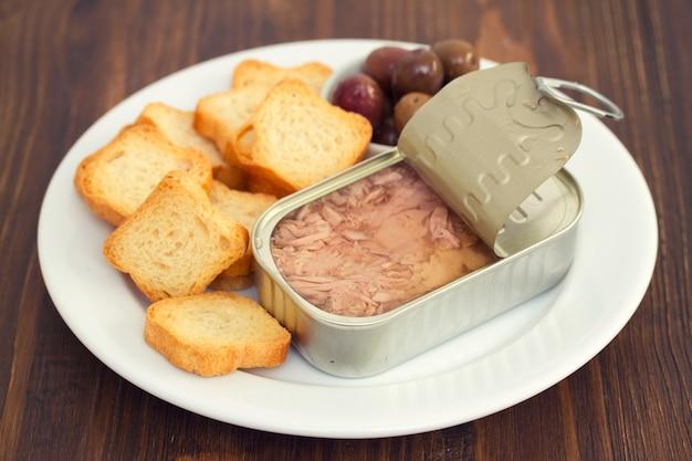 Tuńczyk w żelaznym pudełku z grzankami i oliwkami na białym talerzu