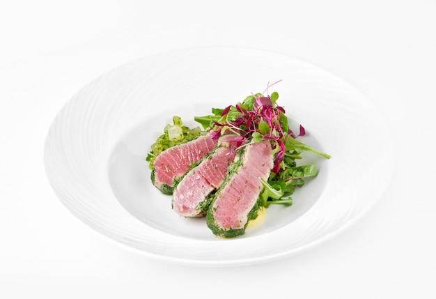 Tuńczyk w ziele z imbirowym melonem na talerzu na białym tle