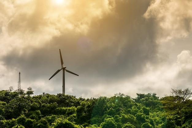Turbina wiatrowa i antena na tle chmury górskiej nieba.