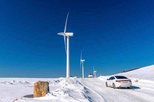 Turbina wiatrowa i samochód z niebieskim niebem w zimowy krajobraz