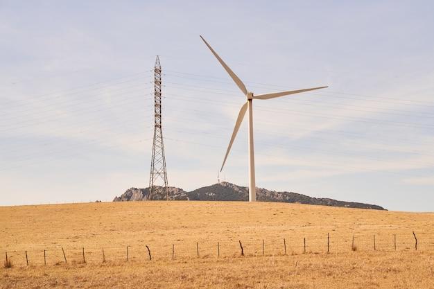 Turbina wiatrowa i wieża wysokiego napięcia. pojęcie energii odnawialnej. kadyks, hiszpania.