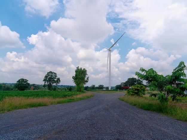 Turbina wiatrowa z zachmurzonym błękitnym niebem w mieście ze skalistą drogą, generator energii elektrycznej z zieloną energią, pole ekologiczne farmy wiatraków