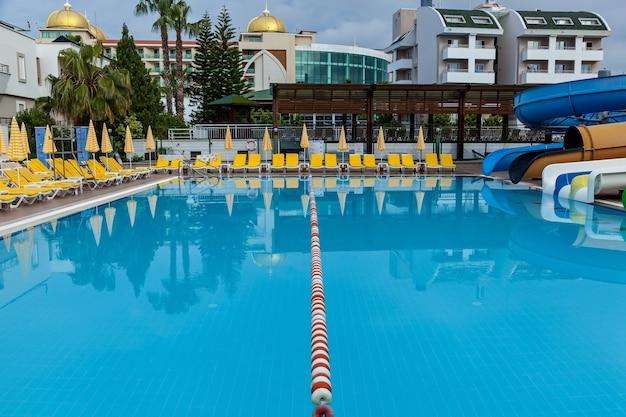 Turcja alanya 05 maja 2019: duży odkryty basen z mnóstwem żółtych leżaków i parasoli po obu stronach w parku wodnym w słoneczny dzień.