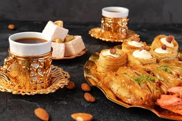 Turecka baklava deserowa z filiżanką kawy na czarnym tle
