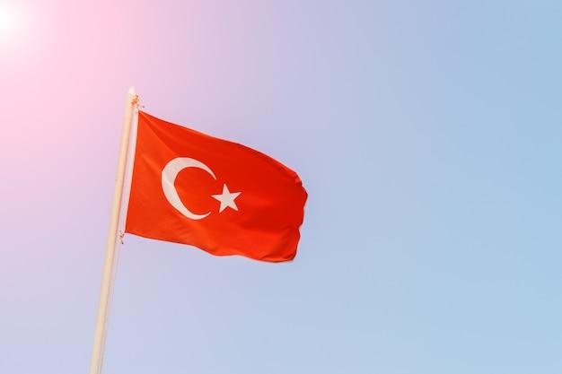 Turecka flaga na tle nieba w słoneczny dzień.