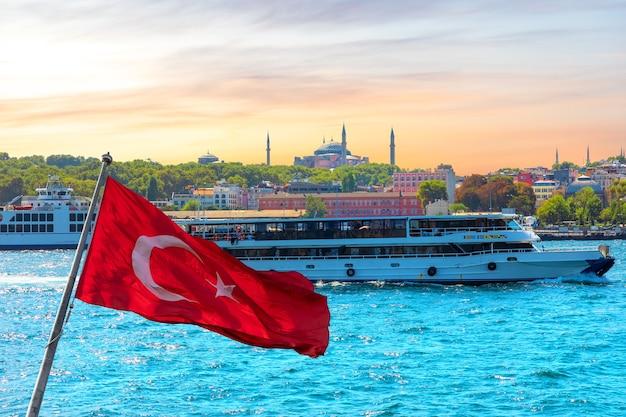 Turecka flaga, w tle statek na bosforze i hagia sophia, stambuł, turcja.