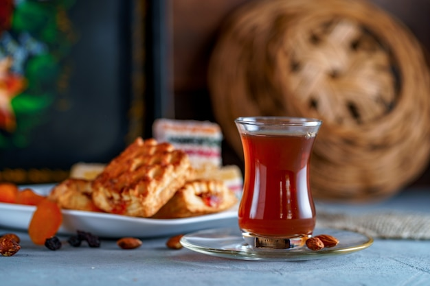 Turecka herbata w autentycznej szklance ze słodyczami, suszonymi owocami i orzechami na podwieczorek