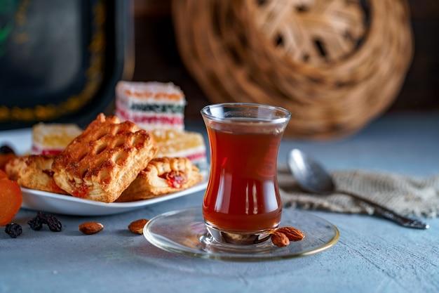 Turecka herbata w tradycyjnym szkle ze słodyczami, suszonymi owocami i orzechami na podwieczorek
