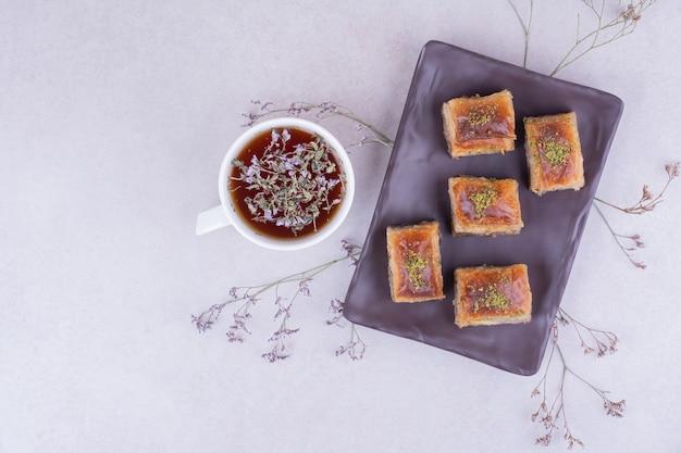 Turecka pakhlava na czarnej ceramicznej tacy z filiżanką herbaty ziołowej.