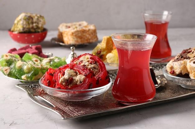 Turecka rozkosz i herbata z granatu na metalowej tacy na szarym tle, zbliżenie, format poziomy