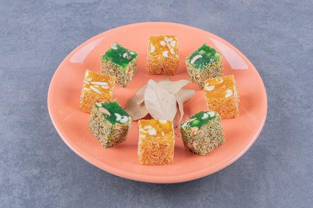 Turecka rozkosz. lokum lub rahat lokum na pomarańczowym talerzu na szarym tle.