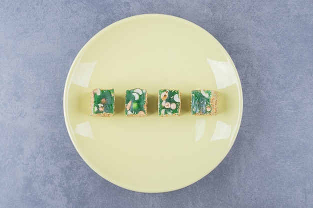 Turecka rozkosz. lokum lub rahat lokum z orzechami laskowymi na żółtym talerzu.